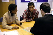 Newly arrived refugee speaks through an interpreter during an interview to assess if it is possibly to gain asylum in the UK. Migrant Helpline, Dover. - Justin Tallis - ,2000s,2005,application,applications,Asylum Seeker,Asylum Seeker,bilingual,black,BME Black minority ethnic,card,cards,communicating,communication,conversation,dialogue,Diaspora,dispersal,dispersing,di
