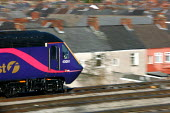 A train travels out of Newport City Centre through residential houses. South Wales - Justin Tallis - 10-02-2006