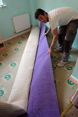 A self employed carpet fitter laying new carpet in a small bedroom. - Justin Tallis - 04-07-2006