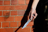 A young man holding a balisong or butterfly knife on a street in Newport, South Wales. This illegal 4 inch long blade can be hidden within the handle and then spun in your hand, opening and closing th... - Justin Tallis - 2000s,2006,adolescence,adolescent,adolescents,against,aggression,aggressive,anger,angry,anti social behaviour,balisong,behavior,behaviour,blade,blades,butterfly,carries,carry,carrying,CLJ Crime Law,cr