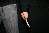 A young man holding a balisong or butterfly knife on a street in Newport, South Wales. This illegal 4 inch long blade can be hidden within the handle and then spun in your hand, opening and closing th... - Justin Tallis - ,2000s,2006,adolescence,adolescent,adolescents,against,aggression,aggressive,anger,angry,anti social behaviour,balisong,behavior,behaviour,blade,blades,butterfly,carries,carry,carrying,CLJ Crime Law,c