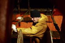 Working through the night on board a fishing trawler in the Irish Sea. The four-man crew work on one of the last remaining trawlers in Fleetwood, Lancashire. - Justin Tallis - 2000s,2006,at,board,boat,boats,common,crew,crewman,crewmen,crewmenmaritime,dark,EARNINGS,EBF,EBF Economy,Economic,Economy,EQUALITY,fisheries,fisherman,fishermen,fishery,fishing,Fishing Industry,Income