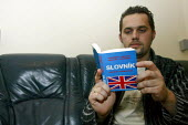 Slovak man learning English in rented accommodation on his day off. - Justin Tallis - 19-11-2006
