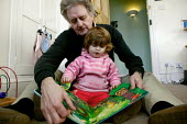 Toddler Grace aged one and a half reading a pop up book with her grandfather on the floor at home. - Justin Tallis - 22-01-2007