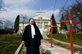 Mother superior standing in front of her convent next to the Stations of the Cross. Jibou, Romania. - Justin Tallis - 17-03-2007