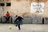 A boy playing football in the street. An impoverished Roma Gypsy community in the town of Jibou, Romania. - Justin Tallis - 15-04-2007
