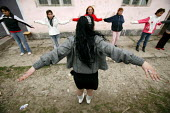 Roma gypsy children exercising in the street, outside their community centre. - Justin Tallis - 2000s,2007,active,activities,activity,arm,arms,BAME,BAMEs,BME,bme minority ethnic,bmes,center,centers,Centre,centres,child,CHILDHOOD,children,class,communicating,communication,communities,community,di