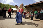 A Roma gypsy transvestite dancing in the street, in the town of Jibou, Romania. - Justin Tallis - 15-04-2007