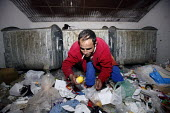 A man scavenging through the bins for food. An impoverished Roma Gypsy community in the town of Jibou, Romania. - Justin Tallis - 17-04-2007