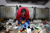 A man scavenging through the bins for food. An impoverished Roma Gypsy community in the town of Jibou, Romania. - Justin Tallis - ,2000s,2007,apple,apples,BAME,BAMEs,bin,bins,BME,bme minority ethnic,bmes,check,checking,cigarette,cigarettes,communities,community,disposal,diversity,Eastern,EQUALITY,ethnic,ethnicity,eu,Europe,europ
