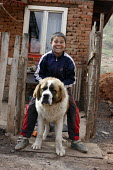 A Roma boy sitting on his large dog. An impoverished Roma Gypsy community in the town of Jibou, Romania. - Justin Tallis - 07-04-2007