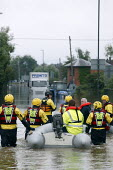 Emergency service workers helping people cross a badly flooded road in Tewkesbury, Gloucestershire, where both The River Avon and River Severn burst their banks. A months worth of rain has fallen in j... - Justin Tallis - 23-07-2007