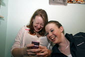 Teenage girls hanging around at home sending text messages on a mobile phone. - Justin Tallis - 09-07-2008