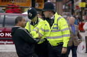 Policemen restraining a man by the arms and pushing him to sit down. Nottingham. - Justin Tallis - 16-07-2008