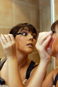 Young woman doing her make up at home before a night out. - Justin Tallis - 12-10-2008