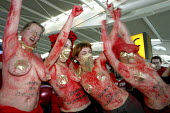 Women coverd in red paint at a Flash Mob Protest At Heathrow Terminal Five. Simply No Slaughter No Third Runway. London Heathrow Airport. - Justin Tallis - 2000s,2009,5,activist,activists,against,air transport,airline,airport,AIRPORTS,anti,bodies,body,campaign,campaigner,campaigners,campaigning,CAMPAIGNS,carbon,civil disobedience,Climate Change,dance,dan