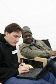 Hackney Migrant Centre volunteer helping a refugee to find a computer course on a laptop. Hackney, London. - Justin Tallis - ,2000s,2009,advice,ADVISE,ADVISER,advisers,advising,advisor,advisors,african,africans,aid,assistance,BAME,BAMEs,bluetooth,BME,BME Black Minority Ethnic,bmes,centre,charitable,charities,charity,cities,