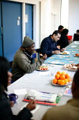 Guests who have come to Hackney Migrant Centre sit and enjoy a free meal. Hackney, London. - Justin Tallis - 25-03-2009