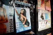 Prostitute calling cards in a London phone box on Soho. - Justin Tallis - 11-06-2009