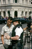 Diplomatic police officers perform a section 44 Stop and Account on an Iranian journalist filming in Parliament Square. London. - Justin Tallis - ,2000s,2009,adult,adults,camera,cameraman,cameras,clj law,crew,crews,evidence,FEMALE,film,filming,force,gathering,harassment,in,Iranian,journalism,journalist,journalists,law,making,male,man,MATURE,med