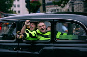Two drunken Celtic FC football fans hang out the window of a taxi cheering on their way to watch the match. London. - Justin Tallis - 2000s,2009,Alcohol,beer,binge,cab,cabs,can,cans,cas,Celtic,cheer,cheering,cider,cities,city,drink,drinker,drinkers,drinking,drinks,drunk,drunken,drunkenness,fan,fans,football,game,having fun,Inebriate