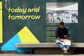 A man sitting on a bench in front of promotional writing for the forthcoming 2012 Olympic Games. Stratford, East London. - Justin Tallis - 22-10-2009