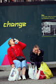 Two women with lots of shopping bags have a rest, sitting on a bench in front of promotional writing for the forthcoming 2012 Olympic Games. Stratford, East London. - Justin Tallis - 22-10-2009