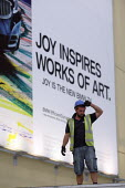 Joy Inspires Works Of Art - BMW Z4 car advertisement behind construction workers erecting marquees for an upcoming event. The O2, London. - Justin Tallis - 03-11-2009