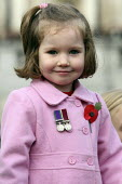 A young girl with medals and a poppy on her pink jacket. Armistice Day in Trafalgar Square. London. - Justin Tallis - 2000s,2009,Armistice,cities,city,COMMEMORATE,COMMEMORATING,commemoration,COMMEMORATIONS,commemorative,Day,EMOTION,EMOTIONAL,EMOTIONS,female,females,girl,GIRLS,HAPPINESS,happy,memories,pink,poppies,pop