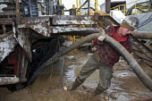 Mancelona, Michigan - A worker struggles with a hose while dismantling a natural gas drilling rig at a well in the Antrim Shale field of northern Michigan. Michigan Basin - Jim West - 08-10-2008
