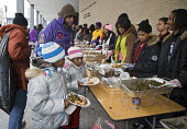 Washington, DC - Volunteers serve food to the hungry at an outdoor soup kitchen. The volunteer project was one of many Martin Luther King Day community service projects. - Jim West - 19-01-2009