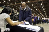 A applicant going over his resume with a recruiter, at a job fair, sponsored by the City of Detroit. - Jim West - 2000s,2009,African American,African Americans,agencies,agency,America,apply,applying,BAME,BAMEs,Black,BME,BME Black minority ethnic American,bmes,career,CAREERS,communicating,communication,conversatio