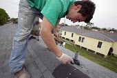 New Orleans, Louisiana - An Americorps volunteer patches the roof on a house being renovated a house in the lower ninth ward damaged by Hurricane Katrina. The house was one of many throughout the city... - Jim West - 01-04-2009