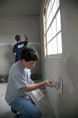 New Orleans, Louisiana - Volunteers from Vianney and St. Marys Catholic high schools in St. Louis repair a house damaged during Hurricane Katrina. They are using joing compound to fill cracks between... - Jim West - 26-03-2009