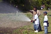 A man directs two boys using a fire hose to water part of an urban farm in a city park. The farm is operated by the nonprofit Detroit Black Community Food Security Network (DBCFSN), USA. - Jim West - 2000s,2009,African American,African Americans,AGRICULTURAL,agriculture,America,BAME,BAMEs,black,BME,BME Black minority ethnic American,bmes,boy,boys,child,CHILDHOOD,children,cities,city,communities,co