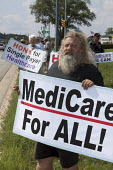 Southfield, Michigan, USA People hold placards along a busy highway supporting national healthcare reform, and especially supporting a single payer plan and medicare for all - Jim West - 18-08-2009