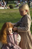 Two young girls wearing period costumes, while one girl braids another's hair.The Mormon church has restored much of the town of Nauvoo to the way it looked when Mormon pioneers lived there in the 184... - Jim West - 08-07-2009