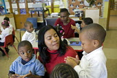 A teacher and pupils in a nursery class at Crary Elementary school, USA. - Jim West - 2000s,2008,African American,African Americans,America,BAME,BAMEs,black,BME,BME Black minority ethnic American,bmes,boy,boys,CARE,carer,carers,child,CHILD CARE,childcare,CHILD-CARE,CHILDHOOD,CHILDMINDI