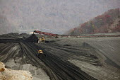 Sylvester, West Virginia USA- Bulldozers spread coal sludge on a coal impoundment dam at Massey Energys Elk Run complex. Impoundments hold liquid and solid wastes from the coal mining process, includi... - Jim West - 09-11-2009