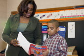First grade teacher helps a student at MacDowell Elementary School. Detroit USA - Jim West - 1st,2010,2010s,African American,African Americans,African-American,America,BAME,BAMEs,black,BME,BME Black minority ethnic,bmes,boy,boys,child,CHILDHOOD,children,class,classes,classroom,classrooms,comm