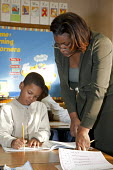 First grade teacher helps a pupil at MacDowell Elementary School. Detroit USA - Jim West - 1st,2010,2010s,African American,African Americans,African-American,America,BAME,BAMEs,black,BME,BME Black minority ethnic,bmes,boy,boys,child,CHILDHOOD,children,class,classes,classroom,classrooms,comm