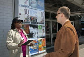 A worker for the U.S. Census Bureau talks to a man on a street about the importance of returning the 2010 Census questionnaire. - Jim West - 10-04-2010
