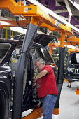 A Chrysler worker installs weatherstripping in new Jeep Grand Cherokee, at the Jefferson North Assembly Plant. - Jim West - 21-05-2010