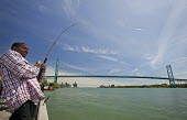 A young man fishes in the Detroit River near the Ambassador Bridge, which links the USA and Canada - Jim West - 15-05-2010
