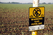 A marker at the edge of a farm field warns of a buried TransCanada natural gas pipeline. - Jim West - 23-05-2010