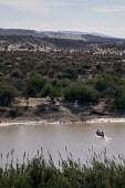 Mexicans cross the Rio Grande in a canoe. The river separates the USA and Mexico. Mexicans illegally cross the river to sell handicrafts to tourists despite threats by U.S. immigration authorities to... - Jim West - 12-10-2010