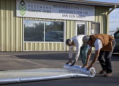 Workers with Veterans Green Jobs prepare rolls of insulation to install in the crawl space below a mobile home. With a grant from the state of Colorado, Veterans Green Jobs does free insulating work i... - Jim West - American,2010,2010s,America,American,americans,assistance,capitalism,capitalist,Colorado,conservation,conserve,crawl,dirty,dust,emissions,employee,employees,Employment,energy,Energy Efficiency,eni,env