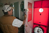A worker with Veterans Green Jobs uses instruments to measure air leaks in a home, prior to doing insulating work. Testing House Leakage with a blower door. An infiltrometer (blower door) is a variabl... - Jim West - American,2010,2010s,air,America,American,americans,assistance,capitalism,capitalist,Colorado,conservation,conserve,emissions,employee,employees,Employment,energy,Energy Efficiency,eni,environment,Envi