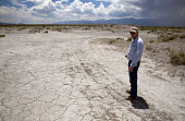 A farmworker stands by a dried up spring, a result of excessive ground water pumping. USA - Jim West - 05-07-2011
