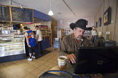 A customer works on his laptop computer at Milagros Coffee House. Profits from the coffee shop support La Puente, a nonprofit agency providing social services in Colorado's San Luis Valley. USA - Jim West - 07-10-2010